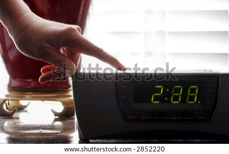 woman holding down the button of a clock radio to set the time
