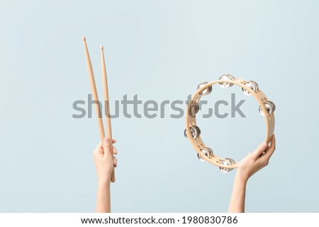 Woman holding drumsticks and tambourine on color background Stock photo ©