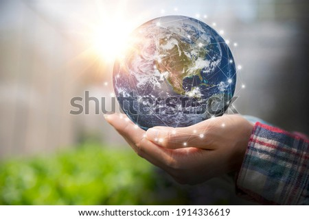 Woman holding earth in her hand, save the earth and energy concept. Earth image courtesy of NASA.