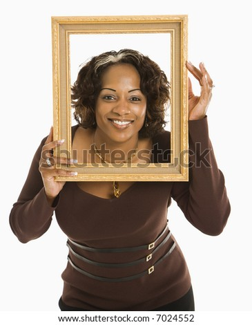 Woman holding empty frame around head smiling.