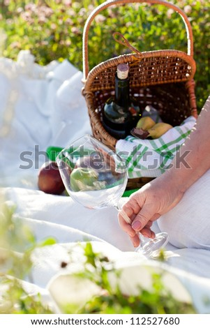 Woman holding empty wineglass, outdoor - stock photo