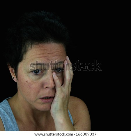 Woman holding face in emotional upset. Mental health/stress/depression. Isolated on black background.
