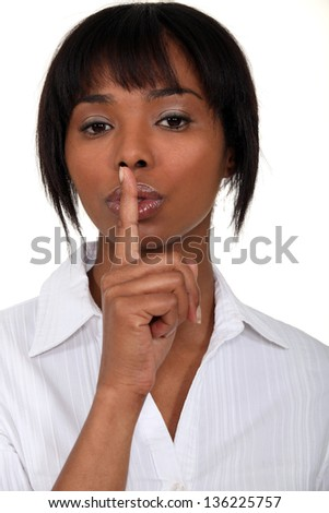 Woman holding finger to lips