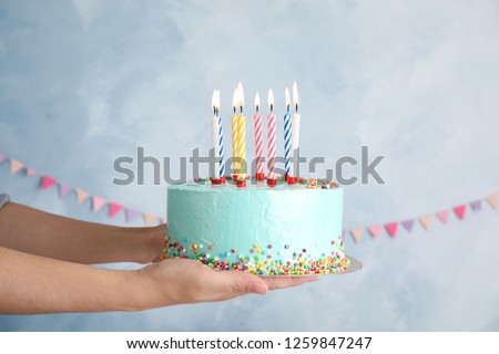 Woman holding fresh delicious birthday cake with candles on color background Foto stock ©