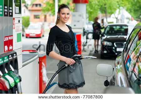 woman holding fuel nozzle in gas station