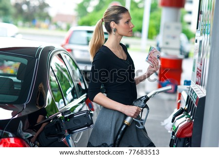 woman holding gas nozzle and money in gas station