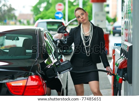 woman holding gas nozzle as gun pointed to her head