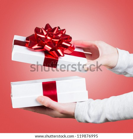 Woman holding gift box close-up with red ribbon against white background