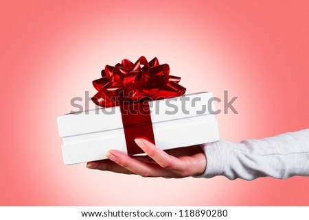 woman holding gift box with red ribbon against pink background