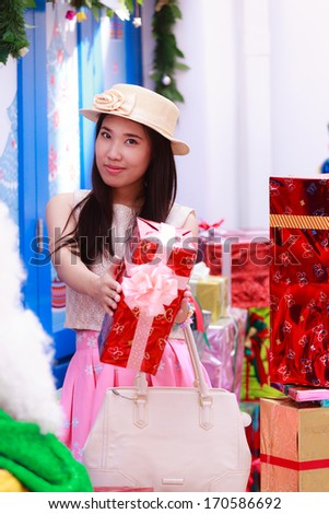 Woman holding giving gift. Happy smiling woman giving you a present being joyful, fresh and cheerful.