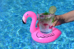 Woman holding glass decorated with pink flamingoes, of sparkling water with a slice of lime, in a pink inflatable flamingo drinks holder in a swimming pool.