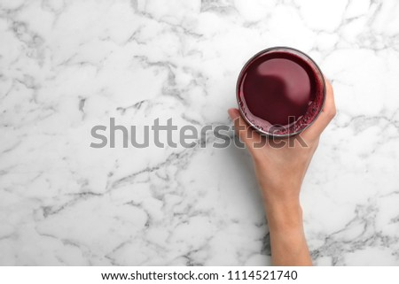Woman holding glass with fresh beet juice on marble table, top view