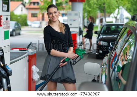 woman holding green nozzle at gas station
