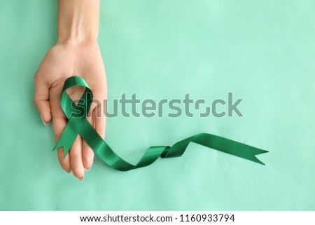 Woman holding green ribbon on color background. Kidneys cancer awareness concept