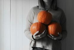 Woman holding Halloween pumpkins in a farmhouse monotone