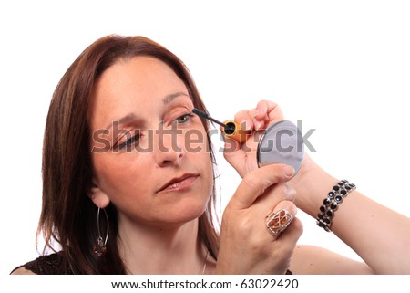 Woman Holding Hand Mirror Applies Mascara To Eyelashes