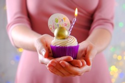 Woman holding happy birthday cupcake with burning candle in purple wrap, cream cheese frosting swirl and golden chocolate decoration on white wooden textured table. Close up, copy space, background.