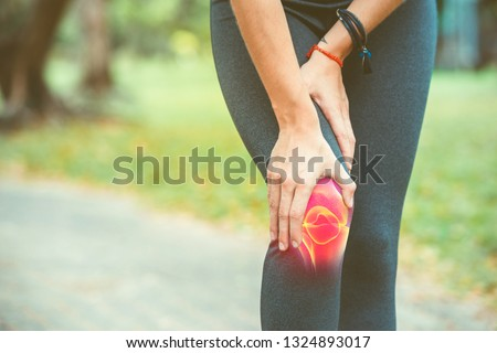 Woman holding her knee with red pain on the skeleton