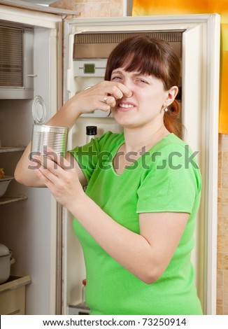 woman  holding her nose because of bad smell near fridge at home