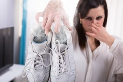 Woman Holding Her Smelling Exercise Shoe With Steam Coming Out From It