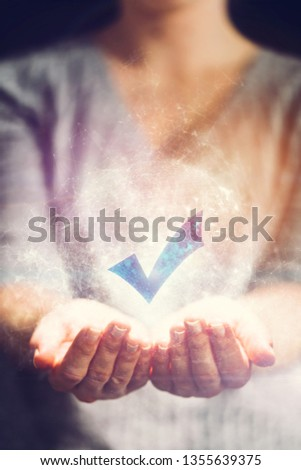 Woman holding hologram with checkmark. OK, yes and confirmation symbol. Agreement, decision and election concept. #1355639375