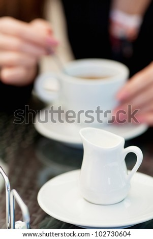 woman holding hot cup of coffee sitting in a cafe