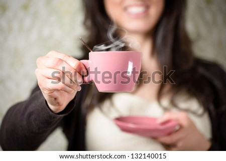 Woman holding hot steaming cup of coffee at home.
