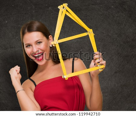 Woman Holding House Frame doing a success gesture against a grunge background