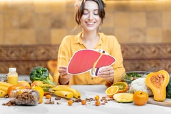 Woman holding human liver model with variety of healthy fresh food on the table. Concept of balanced nutrition for liver health