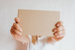 Woman holding in hand small paper box. Young girl with new package. Postal service, delivery. Craft paper. Gift box, present. Box closeup. Blank packing, empty space. People communication. Carton case