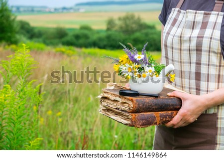 Woman holding in her hands old books, a mortar and magnifying glass. Herbalist collects medicinal plants on a meadow.