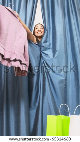 Woman holding jacket and peeking out from dressing room