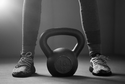 Woman holding kettlebell and standing at gym. Fitness and a healthy lifestyle.