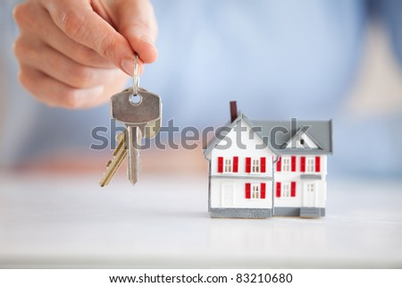 Woman holding keys next to a model house in an office