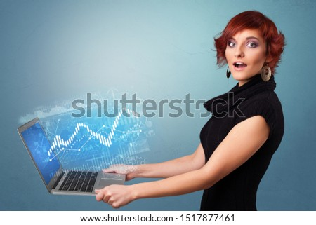 Woman holding laptop projecting financial information, diagrams and charts