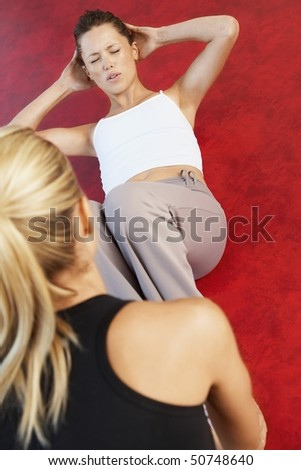 Woman holding legs of woman doing sit ups, high angle view