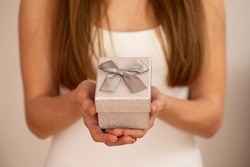 Woman holding little silver box with ribbon on white background. Blurred girl giving present from love. Blonde female showing small gift.