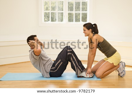 Woman holding man's feet down as he does sit up exercises. - stock photo