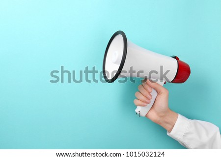 Woman holding megaphone on color background - Shutterstock ID 1015032124