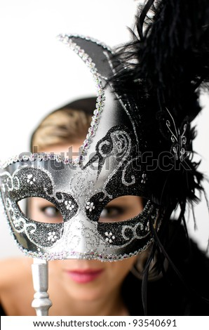 Woman holding metallic gray and black mask in front of her face. Focus is on mask and her face and eyes are blurred.