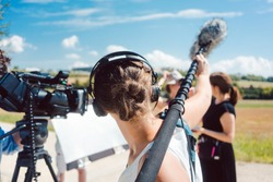 Woman holding microphone on a boom during video production capturing audio