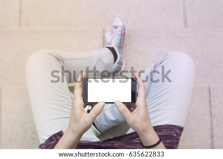 Woman holding modern smartphone. Horizontal mockup. Replaceable with own design. Landscape mode, 16:9 aspect ratio.Top view.