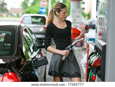 woman holding money when refuel car in gas station