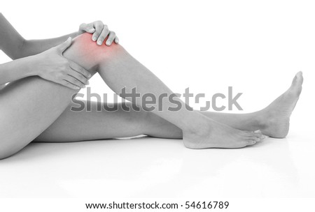 Woman holding on sore knee isolated on white.