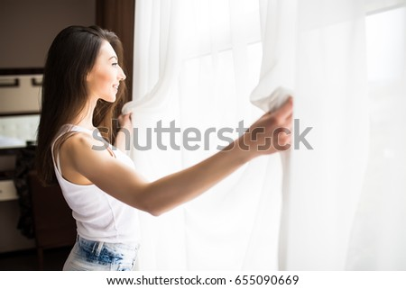Woman holding open curtains while looking out of the window #655090669