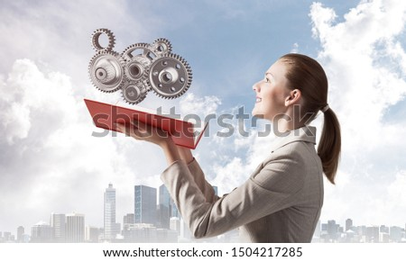 Woman holding open notebook with flying abstract mechanism with cogwheels. Construction and manufacturing concept with virtual reality element. Elegant lady on background of modern cityscape and sky.