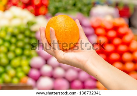 Woman holding orange   in supermarket with a background of lots of fruit