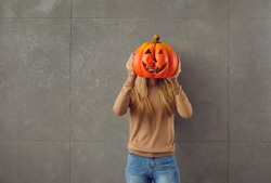 Woman holding orange pumpkin she has made for Halloween party. Young lady hiding face behind carved pumpkin. Studio shot of teenage girl with Jack-o-lantern instead of head standing against grey wall