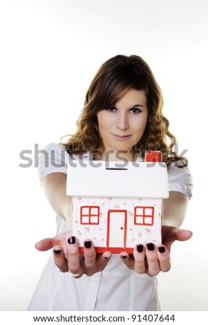 woman holding out in her arms a model house money box to save up for her dream house
