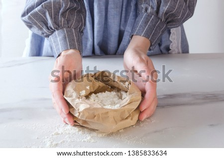 Woman holding paper bag with white flour.Kitchen table and chef next to it, who making preparations for baking
